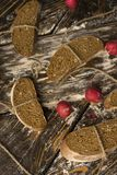 Conceptual still life photography of pieces of bread tied with t. Wine, lying on ancient wooden table made of rough boards among several red radishes. Bakery Royalty Free Stock Image