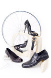 Conceptual still-life with shoes and wheel Stock Photos