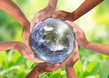 Conceptual symbol of multiracial human hands surrounding the Earth globe. Unity, world peace, humanity concept