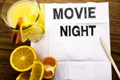 Conceptual text caption showing Movie Night. Concept for Wathing Movies written on tissue paper on the wooden background with pen. Conceptual text caption royalty free stock image