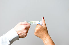 Conceptual Two Hands Holding Euro Bill in Close up Stock Photo