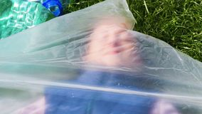 Woman is lying inside a plastic bag. Plastic pollution. Conceptual video on the fight against plastic pollution of the earth. Woman tries to break free from stock video footage