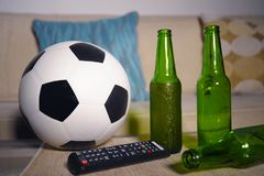 Conceptual watching football game at sofa on television with beer bottles and popcorn bowl in friends enjoying soccer game TV. Conceptual still life no people Stock Photos