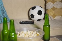Conceptual watching football game at sofa on television with beer bottles and popcorn bowl in friends enjoying soccer game TV. Conceptual still life no people Stock Image
