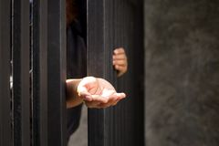 Conceptual woman hand reaching out from metal bars stock photography