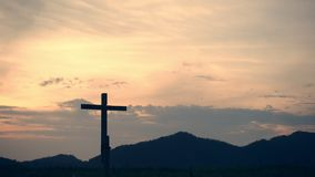 Conceptual wood cross or religion symbol shape over a sunset sky. With clouds background for God. belief or resurrection of god and worship christian. Timelapse stock video