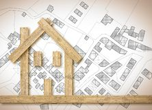 Conceptual wooden house over an imaginary cadastral map of territory with buildings, fields and roads - concept image.  stock photo