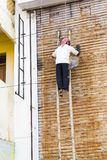 Documentary editorial image. An unidentified man works at heights. Very insecure scaffoldings Stock Image