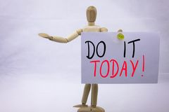 A Conceptual yellow Hand writing caption inscription written sticky note with word Do It TODAY With black ink on a sticky note pin. Ned to a hand of sculpture Royalty Free Stock Photo