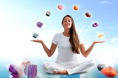 Conceptual yoga with gemstones. Full length portrait of young woman dressed in white doing yoga with precious gemstones.Conceptual dream scape with colorful Royalty Free Stock Image
