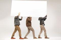 Conceptueel beeld van drie kerels die de raad vervoeren Royalty-vrije Stock Foto