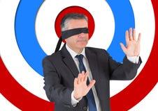 Conceptueel beeld van zakenman met zwarte band op ogen tegen boogschietenraad Stock Fotografie