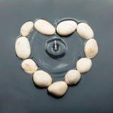 Conceptueel hart van de stenen in het water Stock Foto