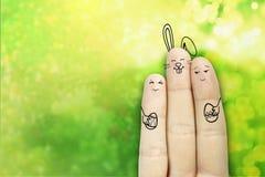 Conceptueel Pasen-vingerart. Het paar met een konijntje houdt geschilderde eieren Het beeld van de voorraad Stock Fotografie