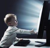 Conceptueel portret van een kleine jongen die een computer met behulp van - Internt-risicosymbool stock foto