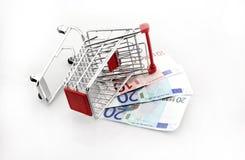 Conceptueel studioschot van een bos van euro bankbiljetten die een boodschappenwagentje op witte achtergrond 18 september, 2016 v Stock Afbeelding