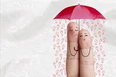 Conceptueel vingerart. De minnaars omhelzen en houden paraplu met dalende bloemen Het beeld van de voorraad Stock Afbeelding