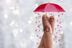 Conceptueel vingerart. De minnaars omhelzen en houden paraplu met dalende harten Het beeld van de voorraad Stock Afbeeldingen