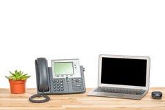 Conceptueel werkruimte of bedrijfsbureauconcept Laptop computer met moderne IP telefoon, installatie in een pot en computermuis o stock afbeeldingen