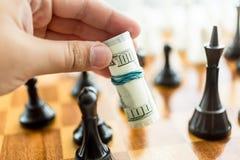 Conceptuele foto van de mens die beweging maken bij schaakspel met dollarbi Royalty-vrije Stock Foto's