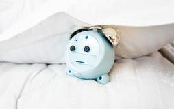 Conceptuele foto van wekker onder hoofdkussen op bed Stock Afbeelding