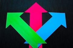 conceptuele gekleurde pijlen op de donkerblauwe textuurachtergrond Stock Afbeelding