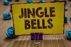 Conceptuele hand die tonend Jingle Bells schrijven Bedrijfsfoto die beroemdste traditioneel Kerstmislied over de hele wereld demo stock foto's