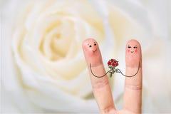 Conceptuele vingerkunst van een Gelukkig paar De mens geeft een boeket Het beeld van de voorraad Stock Foto's