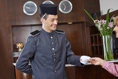 Concergie dans l'hôtel donnant la carte principale à la femme Photos stock