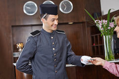 Concergie in hotel giving key card to woman Stock Photos