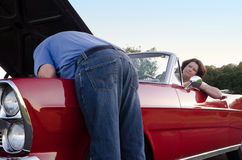 Concern. A woman watches with concern as her husband sticks his head under the hood of their vintage red convertible, trying to fix it Stock Photography