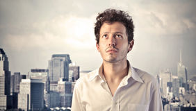 Concern. Young businessman with worried expression and cityscape in the background Royalty Free Stock Image