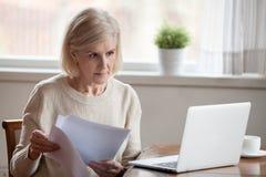 Concerned åldrades kvinnliga dokument för den klara av banken som arbetar på bärbara datorn royaltyfri bild