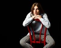 Concerned женщина сидя на красном стуле стоковое изображение rf