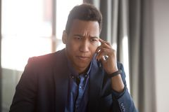 Concerned african American businessman have unpleasant cellphone talk. Concerned african American businessman talk over smartphone think of solving business stock photo