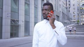 Concerned African American man in white shirt talking by red cell phone standing on the city street. Male businessman or. Manager next to the modern building stock footage
