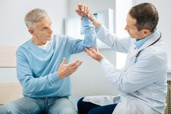 Concerned aged man worrying about his health. What is with me. Concerned anxious aged men holding his hand up and looking at the doctor while worrying about his Royalty Free Stock Images