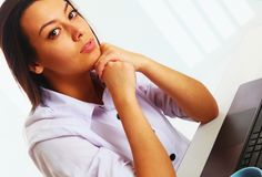 Concerned beautiful businesswoman working at a computer in the. Workplace Royalty Free Stock Image