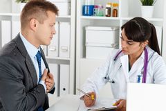 Concerned beautiful female doctor listen carefully businessman p Royalty Free Stock Image