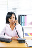 Concerned black businesswoman on phone at desk Stock Photography