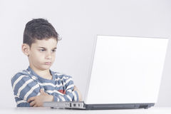 Concerned boy using a laptop computer Stock Photo