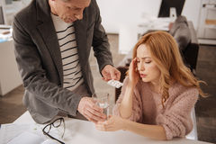 Concerned business colleague offering pills to ill woman at work Royalty Free Stock Photos