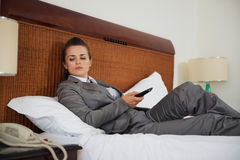 Concerned business woman laying on bed. In hotel room and waiting phone call Stock Photo