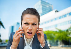 Concerned business woman talking cell phone. Portrait of concerned business woman talking cell phone in office district Royalty Free Stock Image