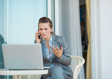 Concerned business woman talking cell phone. On terrace Royalty Free Stock Image