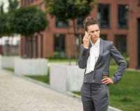 Concerned business woman talking cellphone at office district Stock Photography