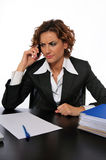 Concerned Business Woman Talking on the Phone. A bothered business woman talking on the phone at her desk Royalty Free Stock Images