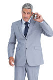 Concerned businessman with alarm clock Royalty Free Stock Photos