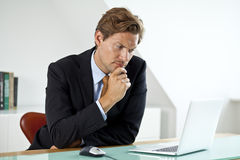 Concerned Businessman in front of laptop Stock Photo