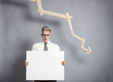 Concerned businessman presenting  panel in front of descending g. Concept: Business crisis. Worried businessman holding white empty signboard with space for text Royalty Free Stock Photography